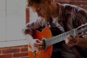 Homem tocando violão com os olhos fechados