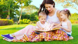 Mães lendo livro com os filhos sentada na grama
