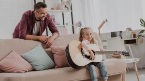 menina e pai tocando violao na sala