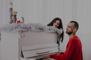 casal tocando piano no natal