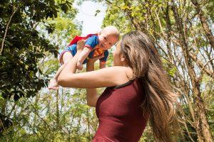 Mães segura filho no alto ao ar livre