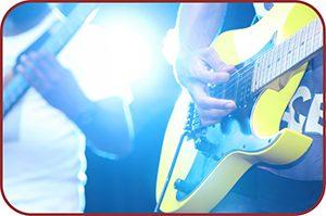 Guitarrista e Baixista no palco com luz ao fundo