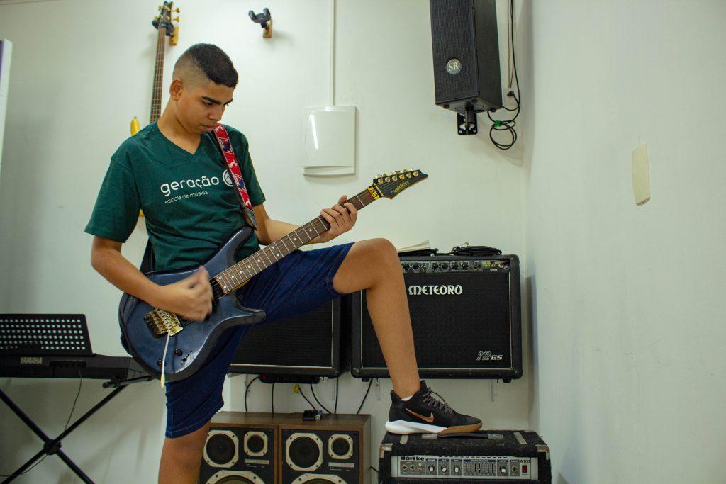 menino negro tocando guitarra